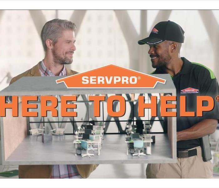 "Two men smiling at each other in an office with the SERVPRO logo and ""Here to Help written in orange letters"